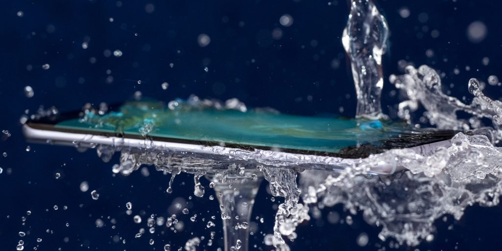 Waterproof phone with water being poured onto it